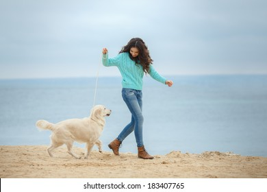 Beautiful woman with her dog playing on the sea shore.