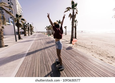 Beautiful woman in her early twenties having some fun with her skaterboard on the promenade by the  beach on a sunny day.