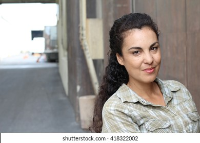 Beautiful woman in her forties wearing a casual plaid shirt in urban background