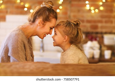 Beautiful woman and her little daughter having fun  indoors