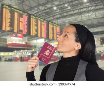 Beautiful woman with her passport in the airport looking the panel