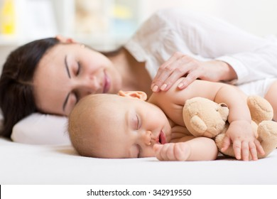 beautiful woman and her son little baby sleeping together in a bedroom