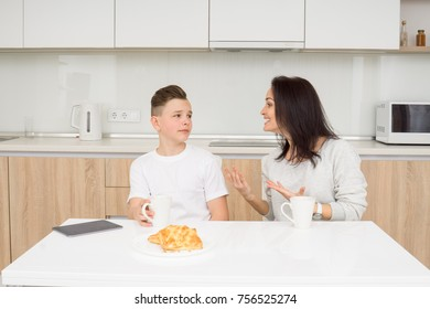 Beautiful woman with her son sitting at table in kitchen. Boy looks displeased while mother scolds him. Copcept of family conflict