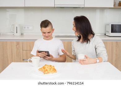 Beautiful woman with her son sitting at table in kitchen. Boy using tablet while mother scolds him. Copcept of family conflict