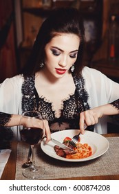beautiful Woman in her underwear eats Italy spaghetti pasta with meat and wine in cafe-restaurant. Dark background. Fashion. Portrait. Close-up.
