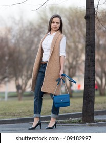 beautiful woman in high heels in beige knitted waistcoat with a blue bag