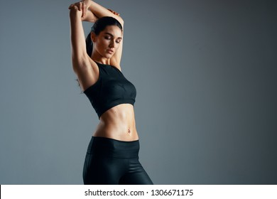 Beautiful woman with a high torso and in a sports suit raised her hands up