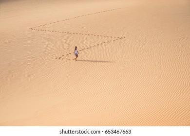 Beautiful woman hiking on giant sand dunes while making a zig zag pattern. Liwa desert, UAE.