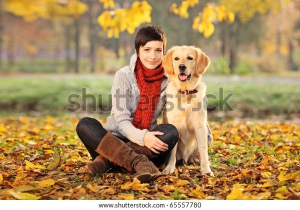 A beautiful woman and his dog (Labrador retriever) posing outside