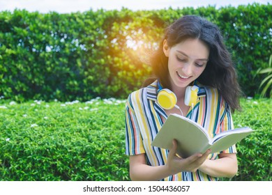 Beautiful woman hold book, reading novel at nice park in summer season. Attractive beautiful lady get fun,  happy, enjoy when she read fun and favorite novel, tree background, copy space