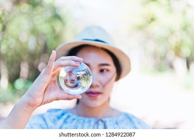 Beautiful woman hold crystal ball and can see a nice view that reflects through the big marble ball. Filtered image.