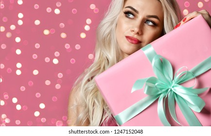 Beautiful woman hold pink and pastel green Christmas presents gift box for new year celebration smiling on pink background with bokeh lights