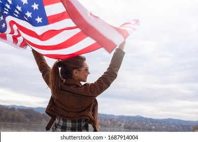 Beautiful woman holding american flag outdoor