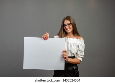 Beautiful woman holding a blank billboard isolated on gray background.