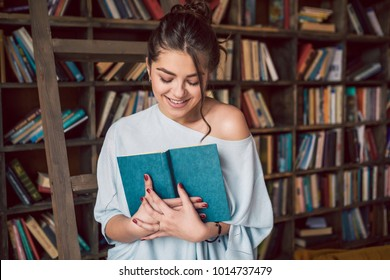Beautiful woman holding book with love