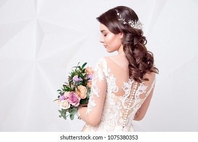 Beautiful woman holding a bouquet of flowers wearing in luxurious wedding dress isolated on background. Concept of wedding hairstyle, makeup and accessories.