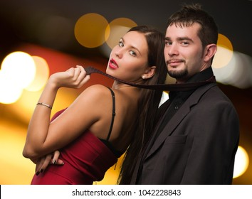 Beautiful Woman Holding Businessman Tie, outdoor