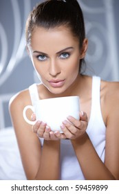 Beautiful woman holding cup on white bed