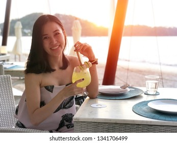 Beautiful woman holding a fruit cocktail on a tropical beach at sunset