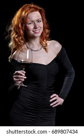 Beautiful woman is holding a glass of wine in her hands