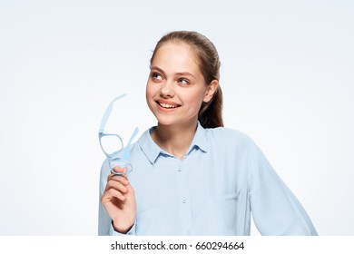 Beautiful woman holding glasses, lost in thought, dreaming, business woman on a light background.