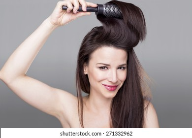 Beautiful woman holding a hair brush in her hair, isolated on a gray background.
