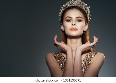 Beautiful woman holding hands near the face of the evening make-up bright dress and a crown with rhinestones