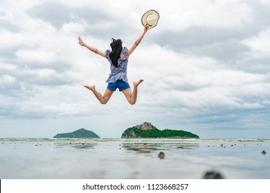 Beautiful woman holding a hat are jumping and happy on the beach in the  summer  holiday.