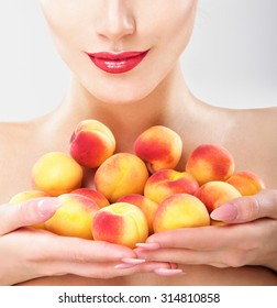 Beautiful woman holding a juicy apricots. Perfect skin. Professional makeup.