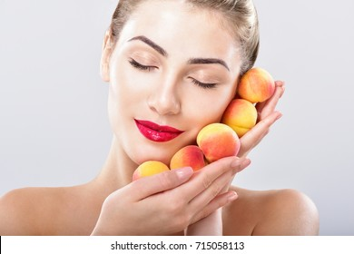Beautiful woman holding a juicy apricots, peaches. Perfect skin. Fruit facial masks. Professional makeup.