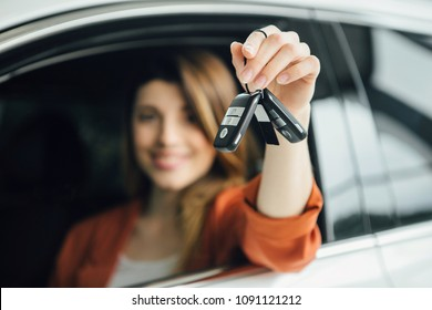 Beautiful woman is holding a key of their new car, looking at camera and smiling.