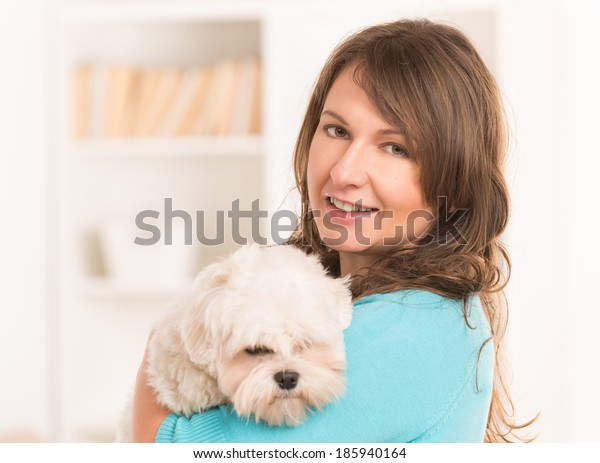 Beautiful woman holding little dog maltese at home