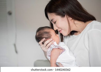 Beautiful woman holding a newborn baby in her arms