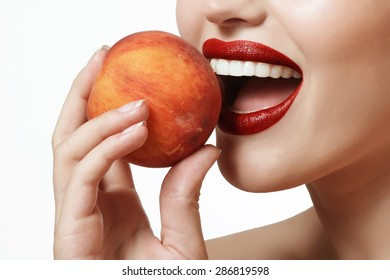 beautiful woman holding a peach in his hand and smiling