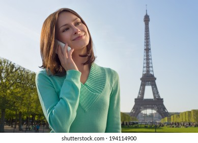 Beautiful woman holding a phone with Eiffel Tower in background