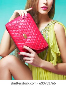 Beautiful woman holding red leather purse. Wearing yellow dress, red manicured nails with lips. Fashion image.