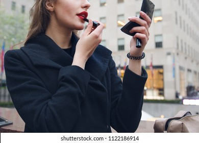 Beautiful woman holding red lipstic and doing quick makeup on the city street
