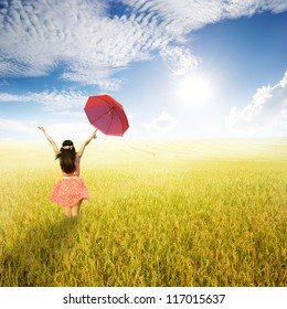 Beautiful woman holding red umbrella in rice field and Sun sky