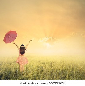 Beautiful woman holding red umbrella in grass field and sunset.Vintage tone.