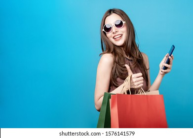 Beautiful woman are holding shopping bags and mobile phonewith face happily in blue seamless,isolated background. Shopping lifestyle, online shopping concept.