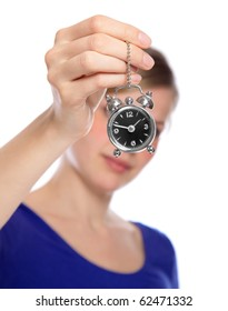 beautiful woman holding a small alarm clock in her hand, isolated on white