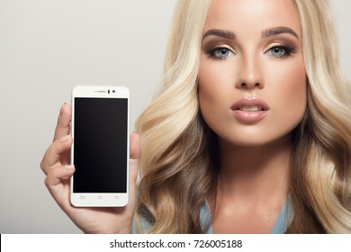 Beautiful woman holding smartphone in hand. Template display. Close-up.