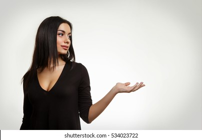 Beautiful Woman Holding Something. Young Female Pointing to Empty Space
