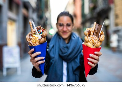 Beautiful woman holding two bubble waffles with ice cream and candies on blue and red paper cones with blurred unrecognizable crowd on the background street in Europe