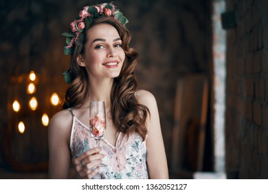 Beautiful woman holding wineglass with rose petals. Celebration concept
