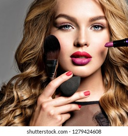 Beautiful woman holds cosmetic tools. Makeup. Beauty concept. Pretty girl with long curly hair.  Fashion make-up.  Closeup portrait. Gorgeous face of an attractive fashion model. Bright red lips.