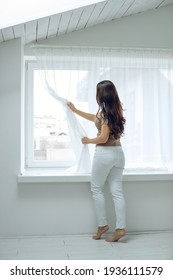 Beautiful woman holds a curtain near the window. The woman looks out the window. High quality photo