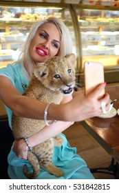 Beautiful woman holds funny calf of lion at table in cafe and makes selfie