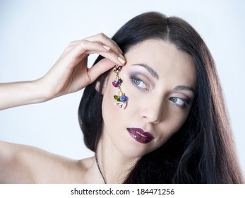 beautiful woman holds the jewels on her face