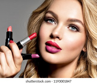 Beautiful woman holds  lipsticks. Makeup. Beauty concept. Pretty girl with long curly hair.  Fashion make-up.  Closeup portrait. Gorgeous face of an attractive fashion model. Bright red lips.
